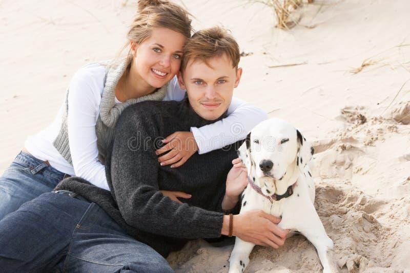 Pares adolescentes románticos en la playa con el perro imágenes de archivo libres de regalías