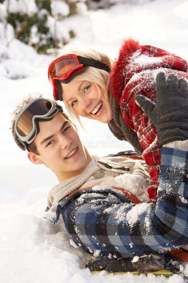 Pares adolescentes románticos que se divierten en nieve foto de archivo