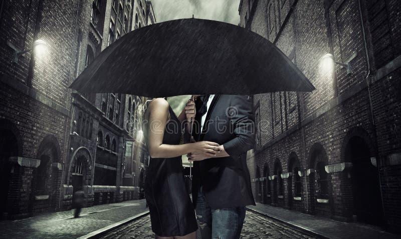 Pares adorables debajo del paraguas imagen de archivo libre de regalías