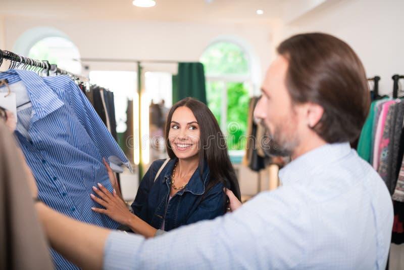 Pares adultos alegres felizes que escolhem a roupa nova na loja fotografia de stock