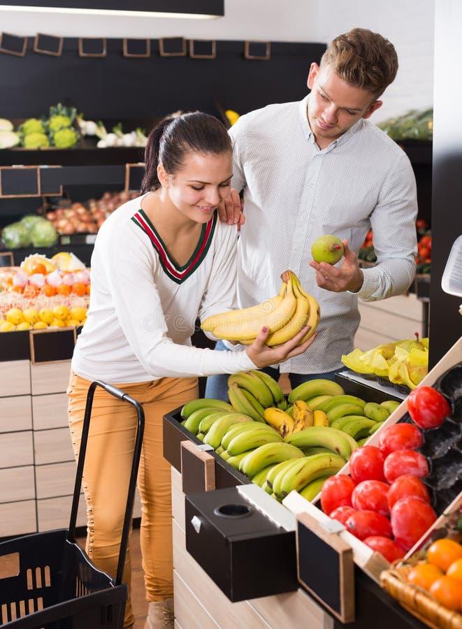 Pares adultos alegres que deciden sobre las frutas en tienda imagen de archivo libre de regalías