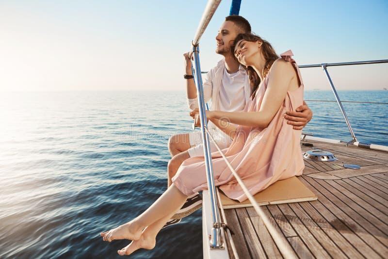 Pares adultos bonitos felizes que sentam-se no lado do iate, olhando no beira-mar e abraçando quando em férias Tan pôde desvanece foto de stock