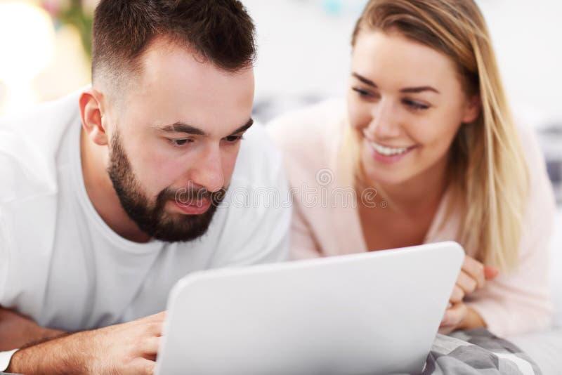 Pares adultos com o laptop na cama fotografia de stock royalty free