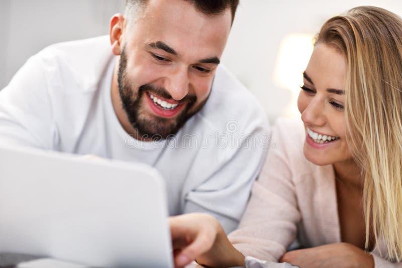 Pares adultos com o laptop na cama imagem de stock royalty free