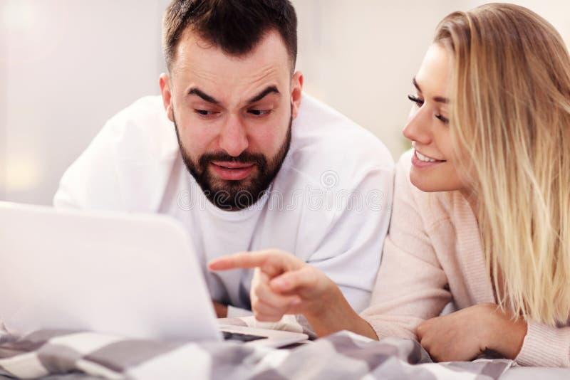 Pares adultos com o laptop na cama imagens de stock royalty free