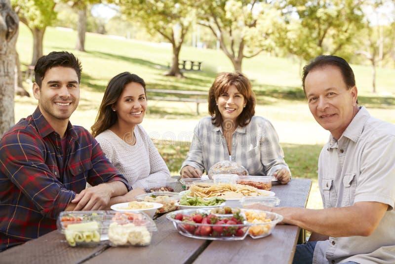 Pares adultos e pais que têm um sorriso do piquenique à câmera fotografia de stock royalty free