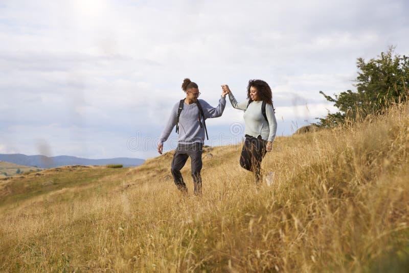 Pares adultos jovenes de la raza mixta que caminan abajo de una colina de común acuerdo durante un alza de la montaña fotos de archivo
