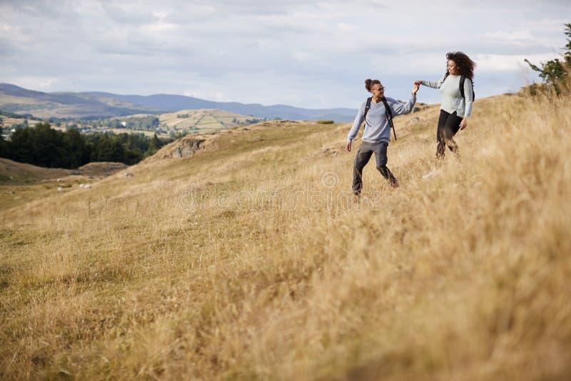 Pares adultos jovenes de la raza mixta que llevan a cabo las manos mientras que camina caminar abajo de una colina durante un alz imagen de archivo libre de regalías