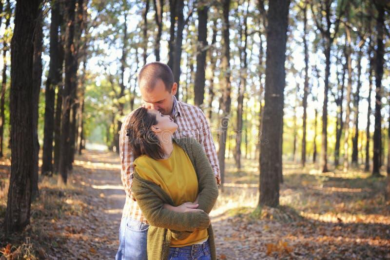 Pares adultos jovenes del amor que caminan en el bosque, familia joven al aire libre, marido para besar a su esposa en pelos foto de archivo libre de regalías
