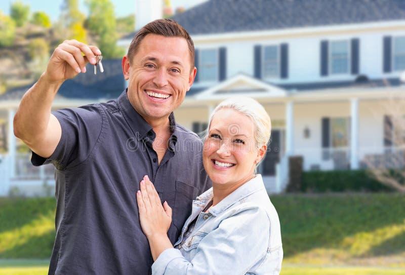 Pares adultos jovenes emocionados con llaves de la casa delante del hogar hermoso imágenes de archivo libres de regalías