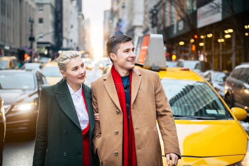 Pares adultos jovenes felices que salen del taxi amarillo en la calle de New York City y que miran al lado foto de archivo libre de regalías