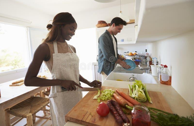 Pares adultos jovenes que preparan la comida para un partido de cena imágenes de archivo libres de regalías