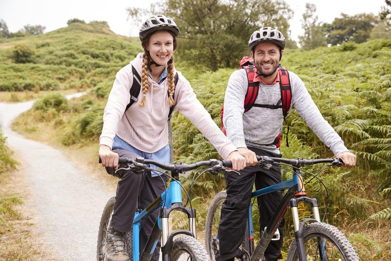 Pares adultos jovenes que se incorporan en las bicis de montaña en un carril del país durante una acampada, cierre imagenes de archivo