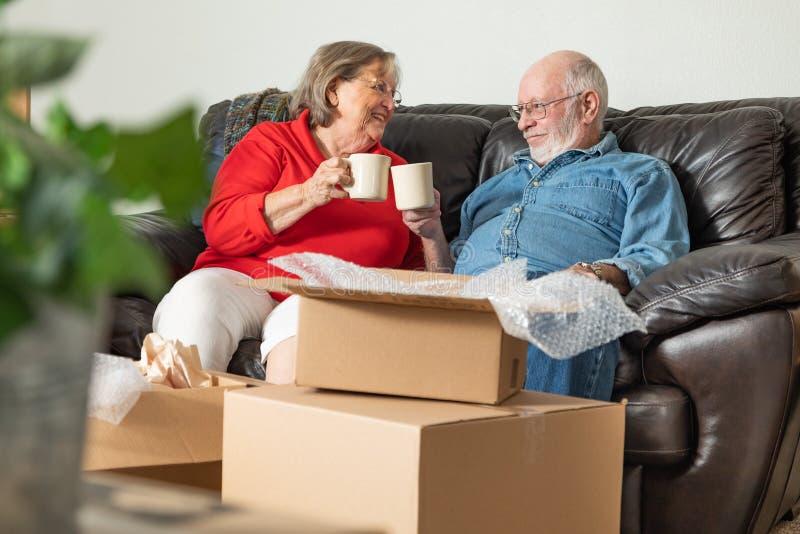 Pares adultos mayores cansados que se relajan en el sofá que goza del café fotografía de archivo