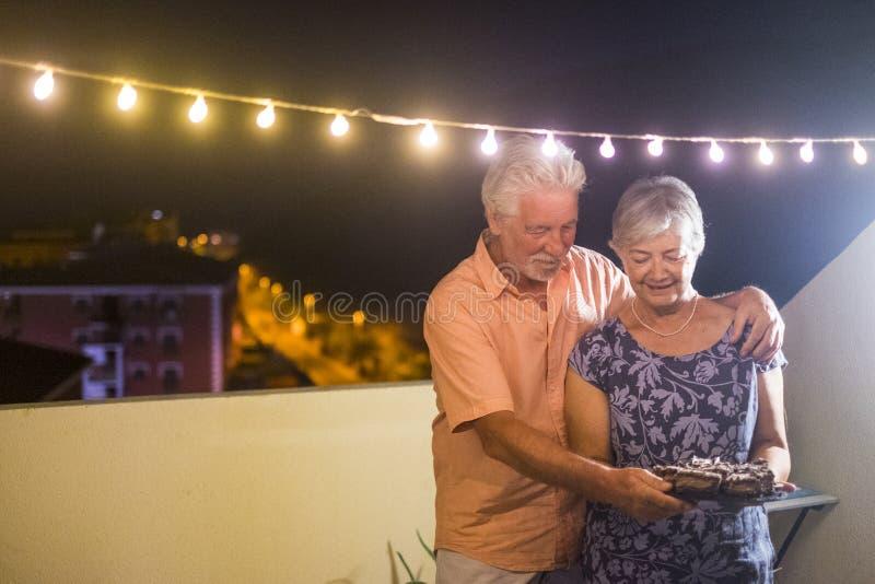 Pares adultos mayores felices con una torta de chocolate después de la cena en casa al aire libre en la terraza con la luz de bul fotografía de archivo