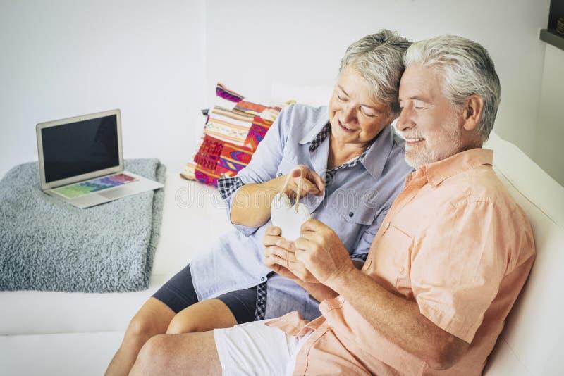 Pares adultos mayores felices de la gente cacuasian en el amor que se sienta en casa en el sof? y que toma un hogar hecho a mano  imágenes de archivo libres de regalías