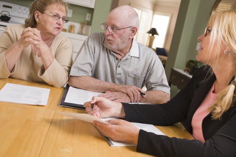 Pares adultos mayores que pasan los papeles en su hogar con el agente fotos de archivo libres de regalías