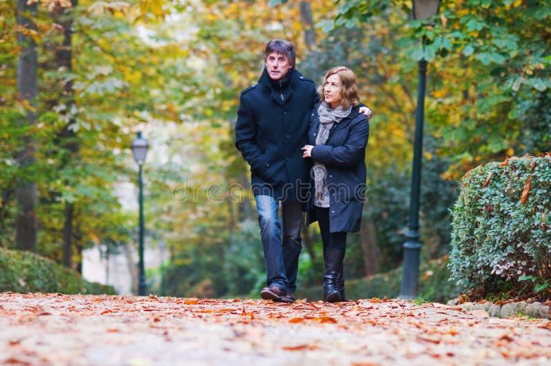 Pares adultos no amor que anda em um parque imagens de stock royalty free