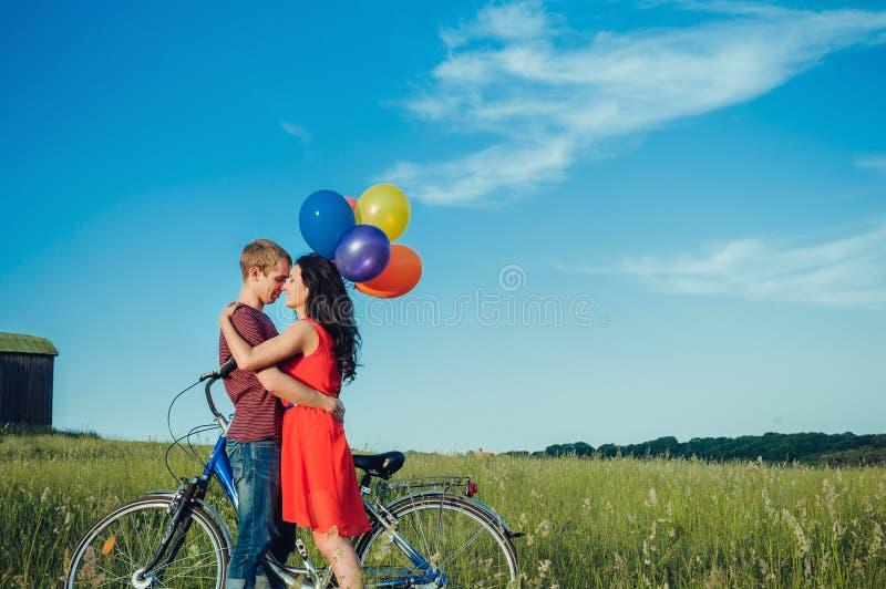 Pares adultos novos felizes no amor no campo Dois, homem e mulher sorrindo e descansando após a equitação da bicicleta fotos de stock