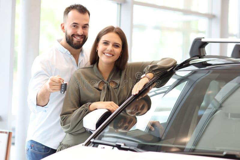 Pares adultos que escolhem o carro novo na sala de exposições imagens de stock