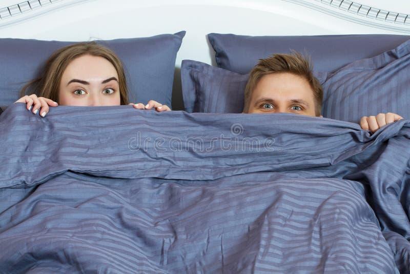 Pares adultos que ocultan debajo de la manta en cama Pares en dormitorio por la ma?ana imágenes de archivo libres de regalías