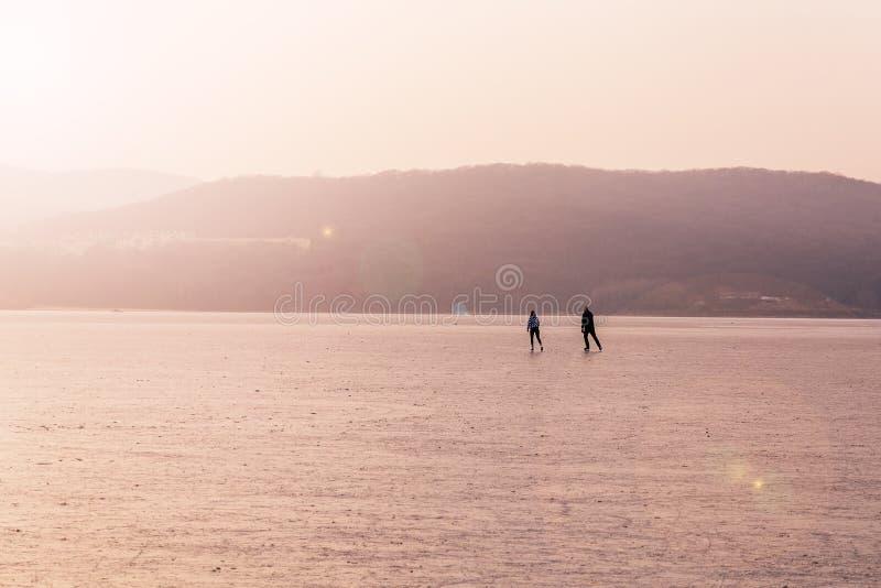 Pares adultos que patinan en una bahía congelada en la puesta del sol foto de archivo