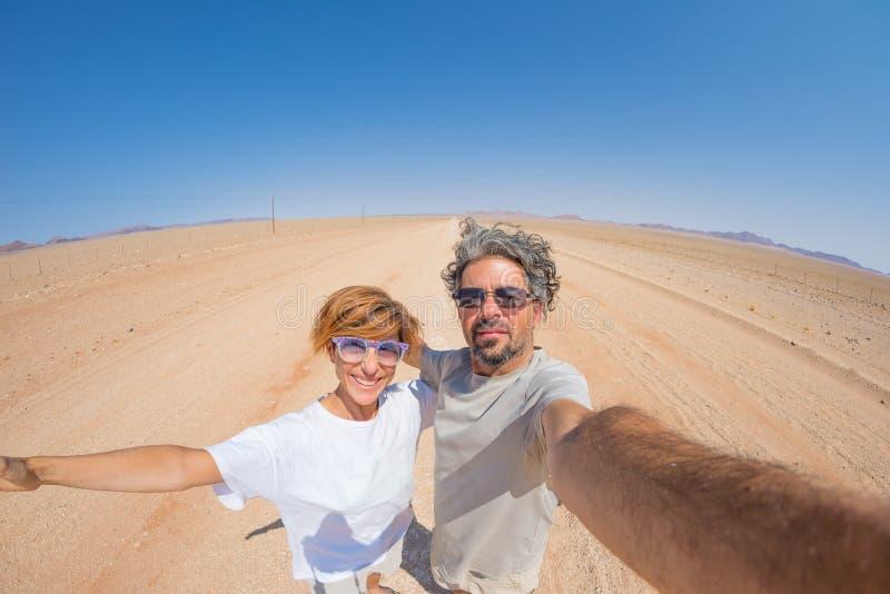 Pares adultos que tomam o selfie na estrada no deserto de Namib, parque nacional do cascalho de Namib Naukluft, destino principal imagens de stock