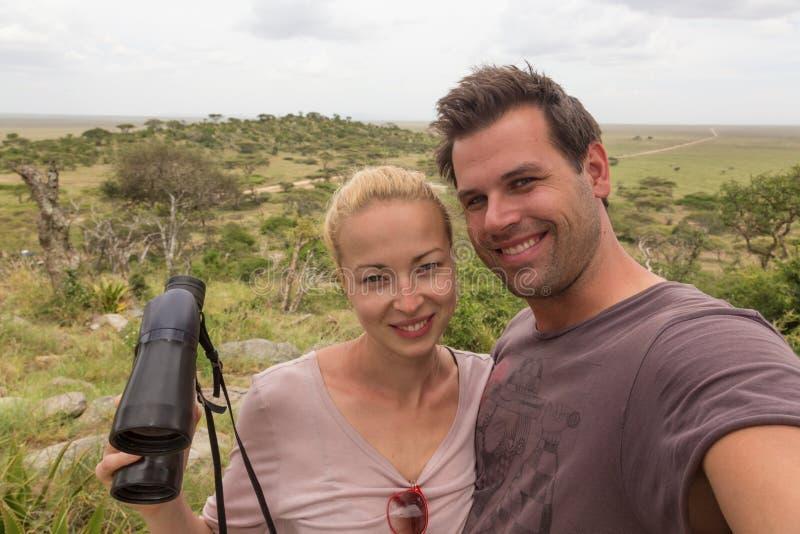 Pares adultos que toman el selfie en safari africano de la fauna en el parque nacional de Serengeti, Tanzania, África fotos de archivo libres de regalías