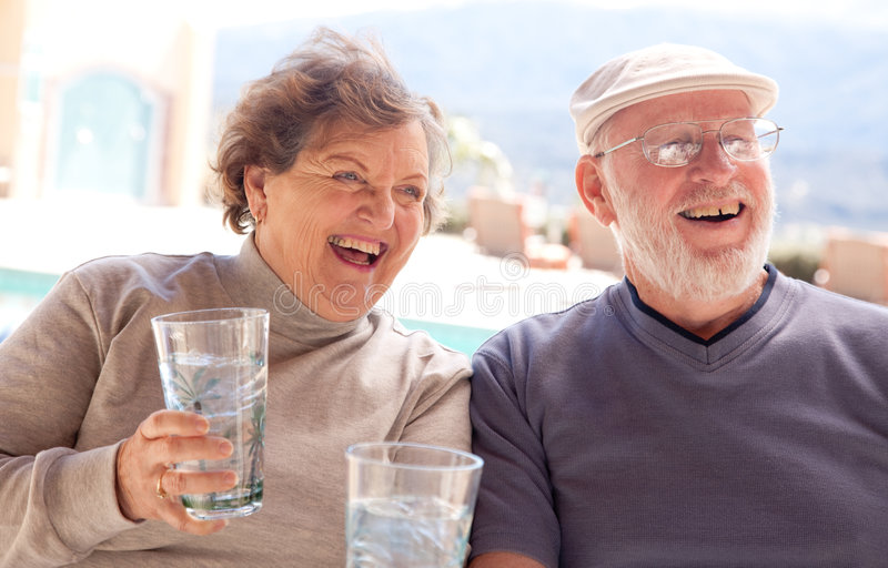 Pares adultos sênior felizes com bebidas foto de stock royalty free