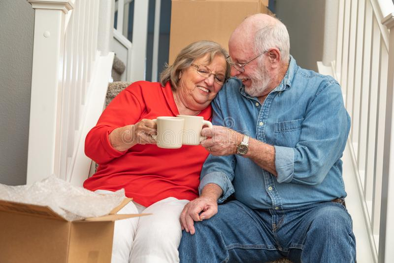 Pares adultos superiores doces em escadas com as canecas de café fotos de stock royalty free