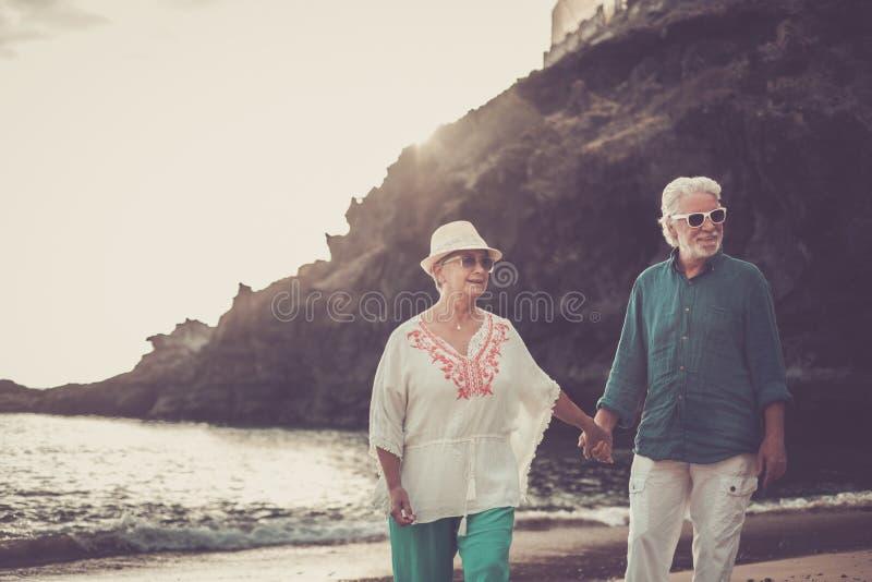 Pares adultos superiores felizes no amor que waing e que sorri apreciando as horas de verão na praia e o estilo de vida aposentad imagem de stock