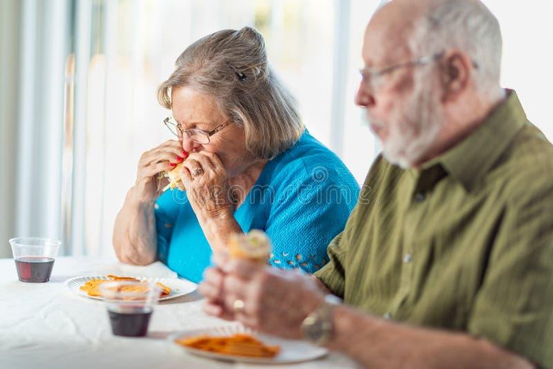 Pares adultos superiores que apreciam sanduíches na tabela fotografia de stock royalty free