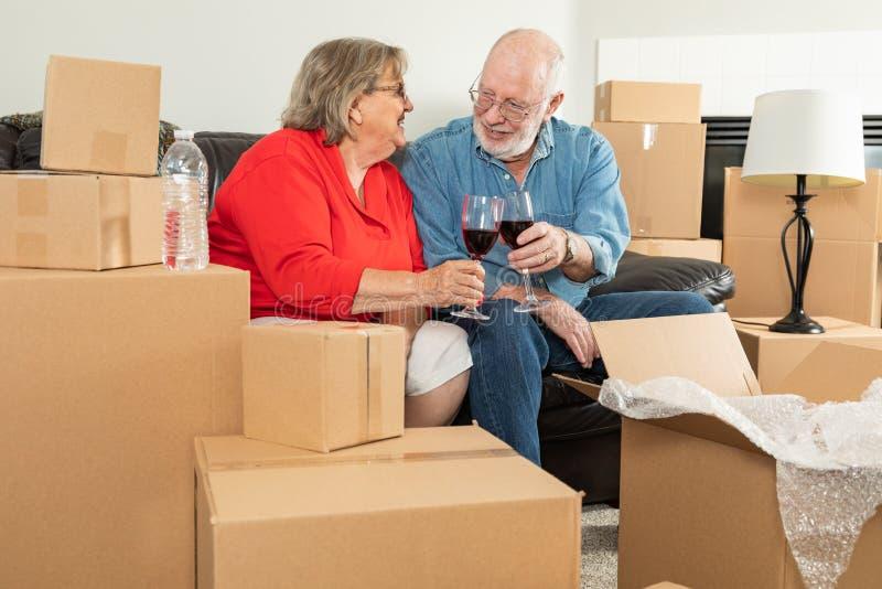 Pares adultos superiores que brindam os vidros de vinho cercados movendo caixas imagem de stock royalty free