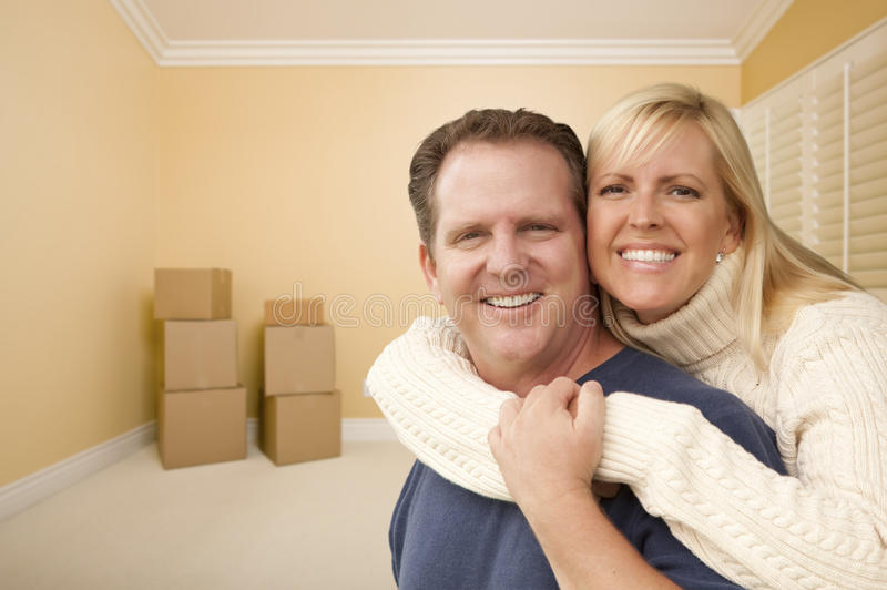 Pares afetuosos felizes na sala da casa nova com caixas foto de stock royalty free