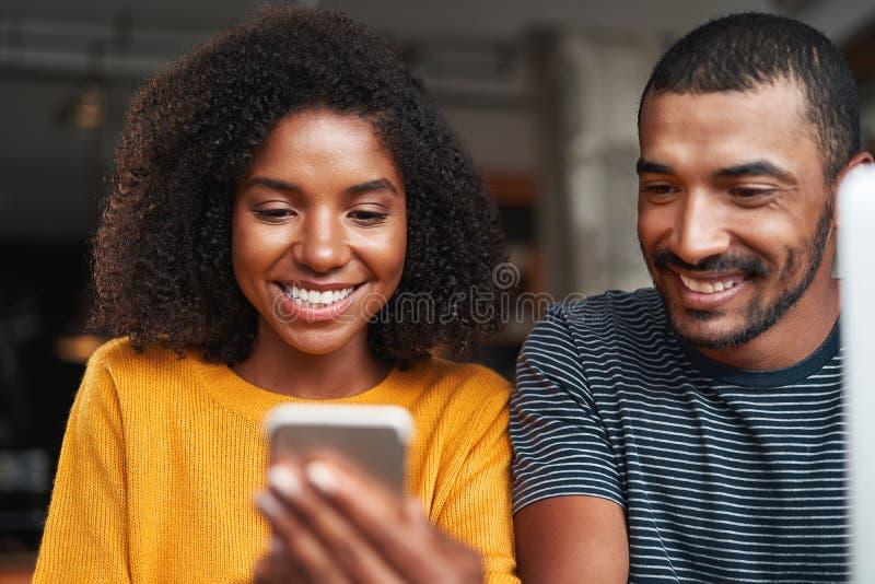 Pares africanos de sorriso que olham o telefone celular fotografia de stock