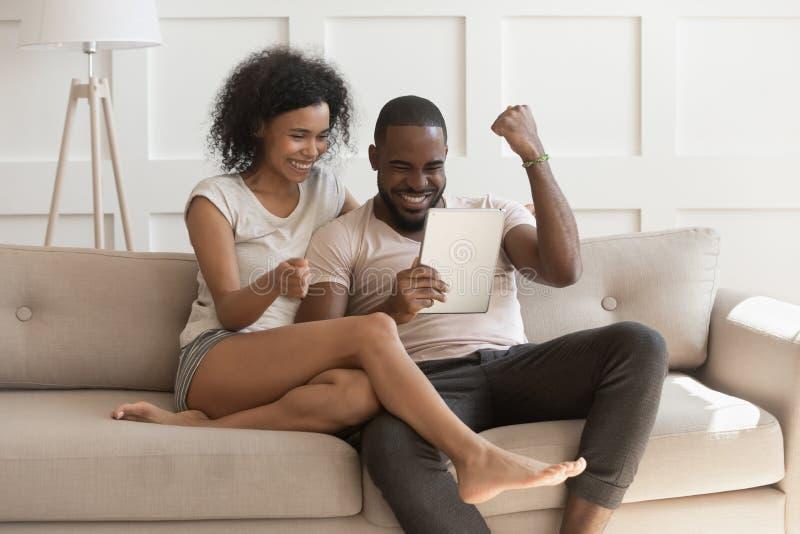 Pares africanos felices emocionados que miran a ganadores digitales de la sensación de la tableta fotos de archivo