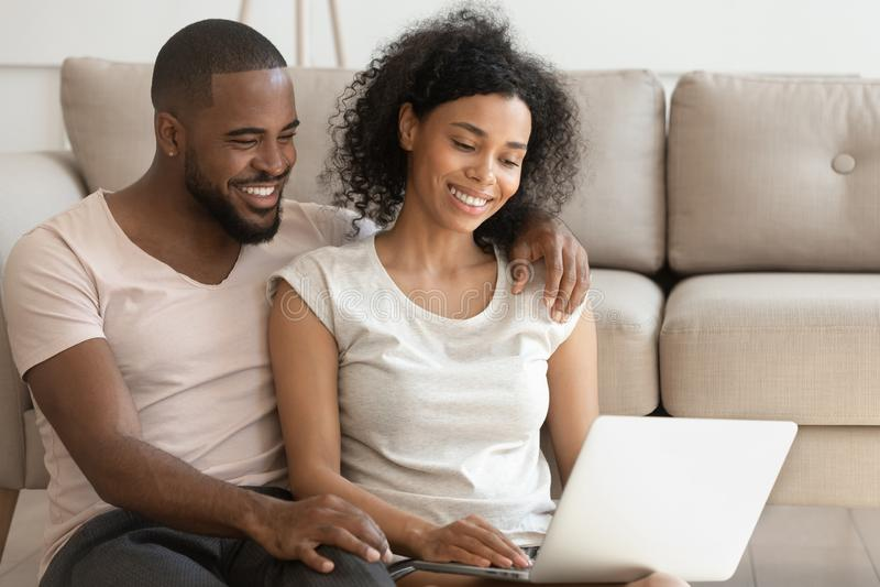 Pares africanos felices usando película de observación del ordenador portátil sentarse en piso imagenes de archivo