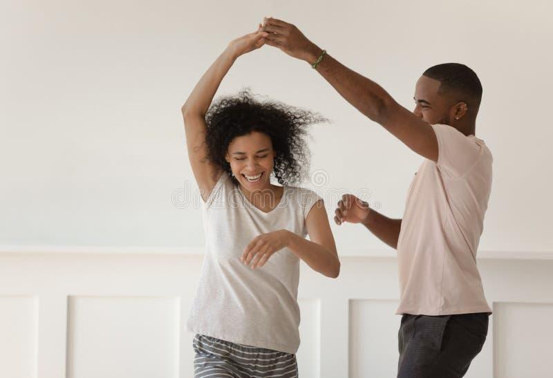 Pares africanos jovenes felices que llevan a cabo el baile de las manos que se ríe del hogar imagenes de archivo