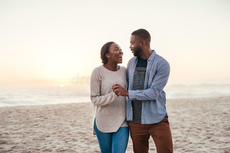 Pares africanos jovenes que caminan en una playa en la risa de la puesta del sol foto de archivo