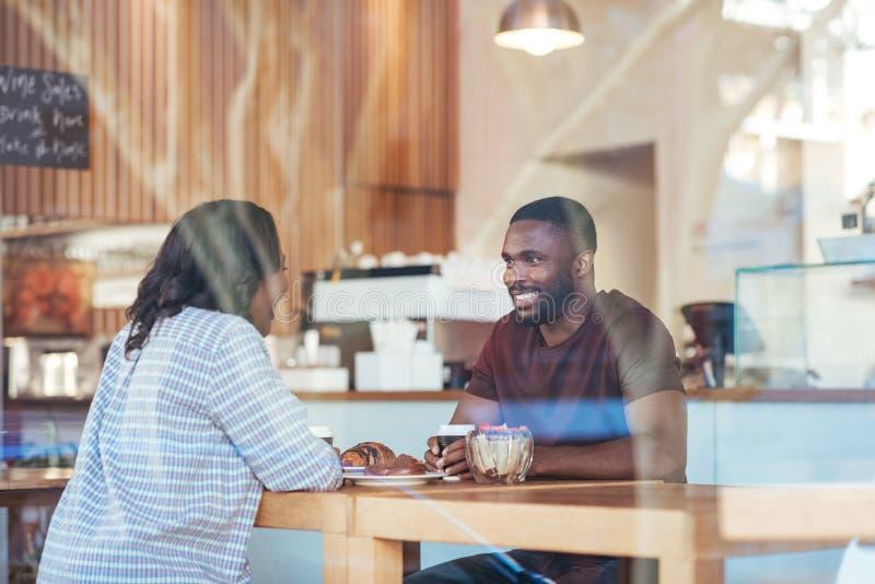 Pares africanos jovenes que hablan junto sobre el café en un café imagenes de archivo