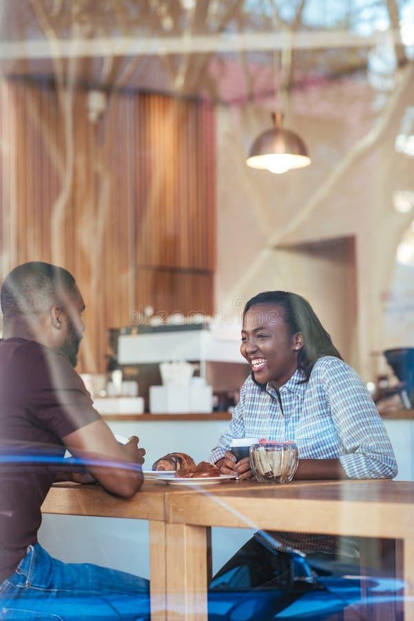 Pares africanos jovenes que hablan mientras que se sienta junto en un café imagen de archivo