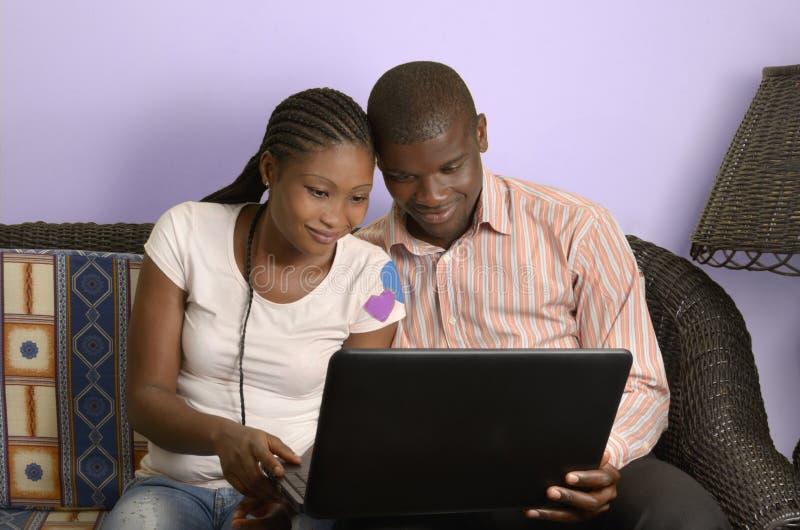 Pares africanos jovenes que practican surf Internet imágenes de archivo libres de regalías