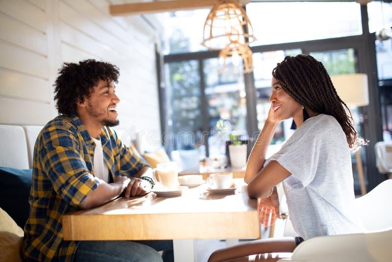 Pares africanos jovenes sonrientes que se sientan en una tabla en un café de consumición del café y que hablan junto fotos de archivo libres de regalías