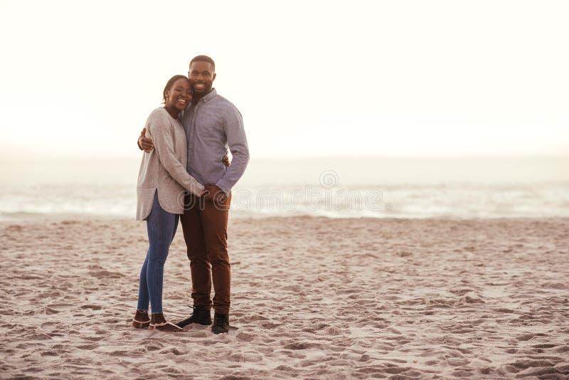 Pares africanos novos de sorriso que estão em uma praia no por do sol fotografia de stock