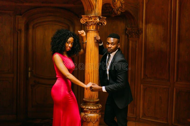 Pares africanos novos lindos que guardam as mãos na coluna do vintage Fundo luxuoso do interior do teatro imagens de stock