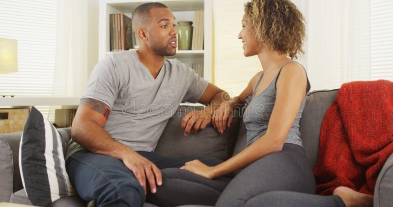 Pares africanos que hablan junto en el sofá fotografía de archivo