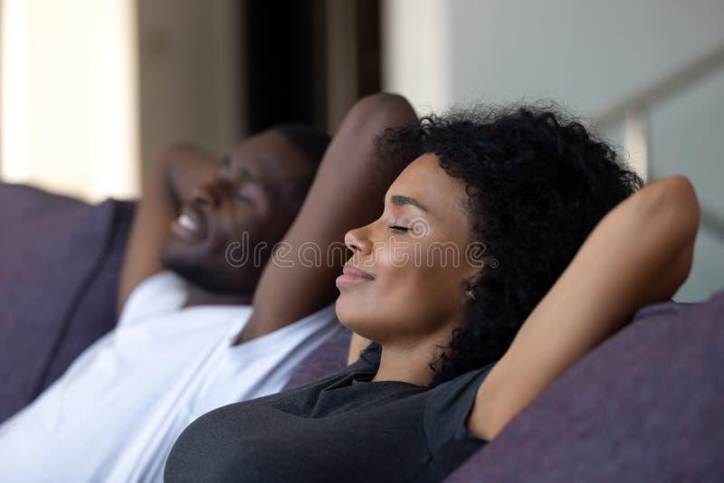 Pares africanos relajados que gozan respirando el aire fresco en el sofá cómodo imagen de archivo