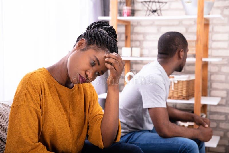 Pares africanos trastornados que se sientan en el sof? foto de archivo libre de regalías
