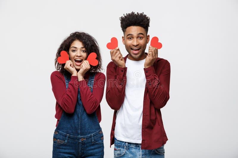 Pares afro-americanos bonitos que guardam o coração de papel de dois vermelhos, olhando a câmera e sorrindo, isolado no fundo bra imagens de stock