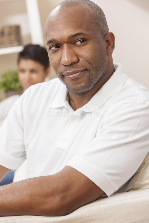Pares afro-americanos consideráveis da mulher do homem que sentam-se em casa imagem de stock royalty free